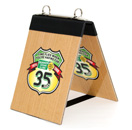 Flip top table tent with logo printed 4 color onto rubberized material, laminated and mounted onto Masonite board.